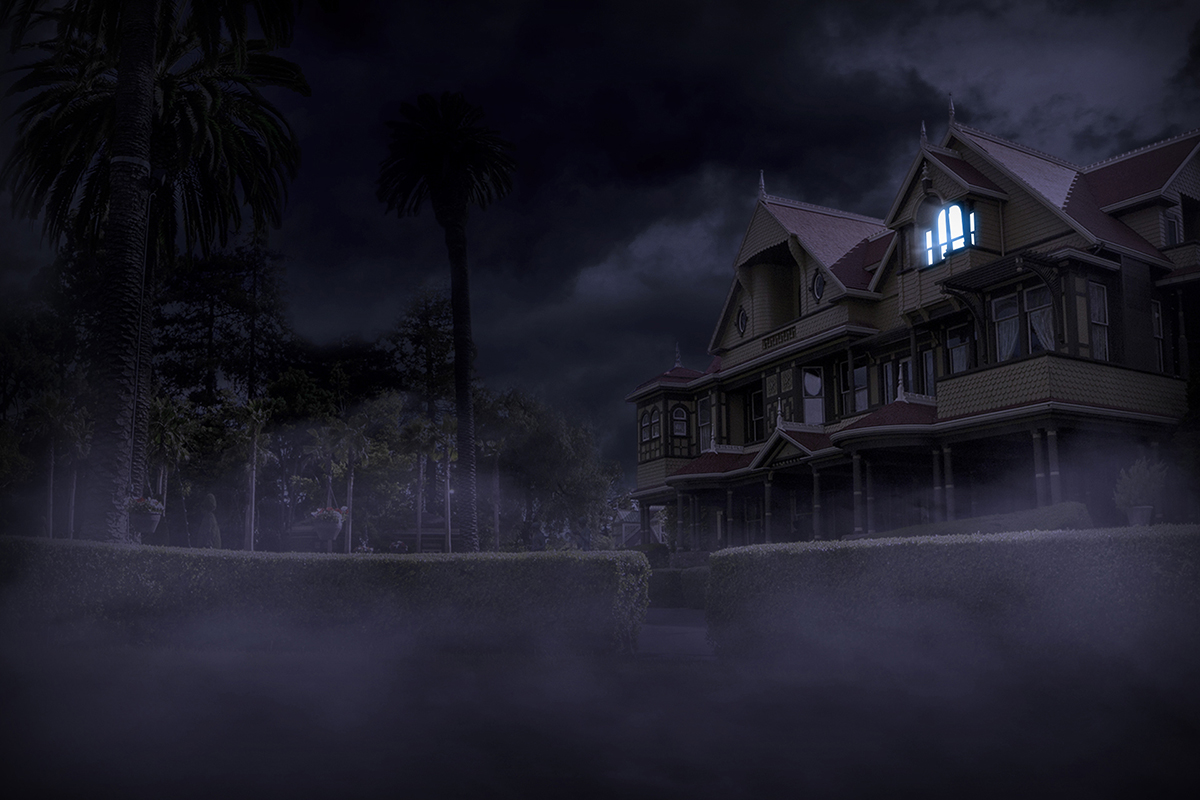 Winchester Mystery House night time with blue light shining from a room.